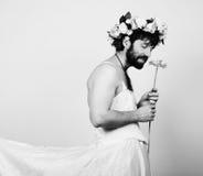 Uomo barbuto in vestito da sposa di una donna sul suo corpo nudo, tenente un fiore Sulla sua testa una corona dei fiori divertent Immagini Stock Libere da Diritti