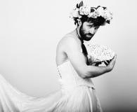 Uomo barbuto in vestito da sposa di una donna sul suo corpo nudo, tenente un fiore Sulla sua testa una corona dei fiori divertent Fotografie Stock Libere da Diritti