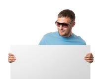 Uomo barbuto in vetri di sole che tengono tabellone per le affissioni bianco Immagine Stock