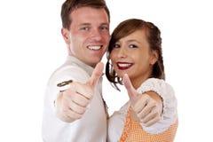 Uomo bavarese e donna che mostrano i pollici in su Fotografia Stock