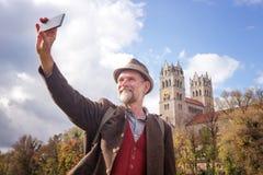 Uomo bavarese nel suo esterno diritto 50s e nella presa del selfie Fotografia Stock Libera da Diritti