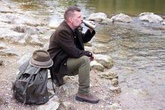 Uomo bavarese nel suo 50s che si siede dal fiume Immagini Stock Libere da Diritti