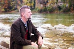Uomo bavarese nel suo 50s che si siede dal fiume Immagine Stock Libera da Diritti