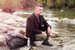 Uomo bavarese nel suo 50s che si siede dal fiume Fotografia Stock