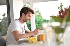 Uomo bello alla tavola di prima colazione che websurfing fotografia stock