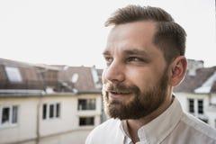 uomo bello barbuto che ha una conversazione che parla nel tramonto e nella camicia bianca fotografia stock