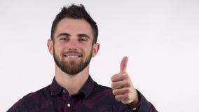 Uomo bello barbuto felice che sorride mostrando i pollici su isolati archivi video