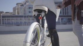 Uomo bello in cappotto marrone che insegna alla sua amica a guidare la bicicletta nella città, sia risata della gente Svago di stock footage