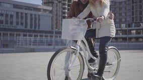 Uomo bello in cappotto marrone che insegna alla sua amica a guidare la bicicletta nella citt?, sia risata della gente Svago di archivi video