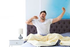 Uomo bello che allunga nella mattina bedtime fotografia stock libera da diritti