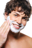 Uomo bello che applica crema da barba sul suo fronte Immagine Stock Libera da Diritti