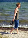 Uomo bello che cammina da solo sulla spiaggia Immagini Stock