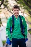 Uomo bello che cammina intorno alla città che sorride e che ascolta la musica in parco Luce molle di tramonto Fotografia Stock Libera da Diritti