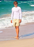 Uomo bello che cammina sulla sabbia della spiaggia della spiaggia con il mare blu su fondo Fotografie Stock