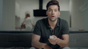 Uomo bello che cerca programma della TV alla cucina Tipo sorridente che fa gesto di vittoria stock footage