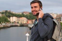 Uomo bello che chiama dal telefono dal porto con lo spazio della copia Fotografie Stock Libere da Diritti
