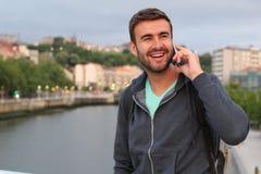 Uomo bello che chiama dal telefono dal porto con lo spazio della copia Fotografia Stock