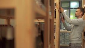 Uomo bello che considera la bottiglia di vino su uno scaffale di legno in negozio di alcolici Il cliente sta scegliendo la bevand stock footage