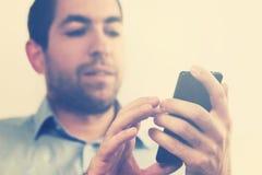 Uomo bello che controlla il suo telefono Immagine Stock Libera da Diritti