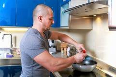 Uomo bello che cucina nella cucina Fotografia Stock Libera da Diritti