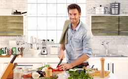Uomo bello che cucina nella cucina a casa Immagini Stock