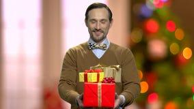 Uomo bello che dà i contenitori di regalo di Natale stock footage