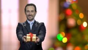 Uomo bello che dà il contenitore di regalo di Natale stock footage