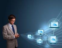 Uomo bello che digita sullo smartphone con la computazione della nuvola Fotografia Stock Libera da Diritti