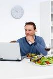 Uomo bello che esamina il suo computer portatile Immagine Stock