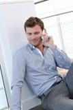 Uomo bello che fa un phonecall che si siede sul pavimento Immagini Stock