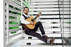 Uomo bello che gioca chitarra sulle scale Maschio serio che si rilassa all'aperto Immagini Stock Libere da Diritti