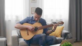 Uomo bello che gioca una chitarra acustica a casa sul sofà archivi video