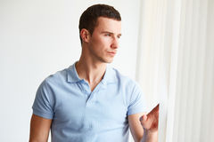 Uomo bello che guarda fuori la finestra Immagine Stock