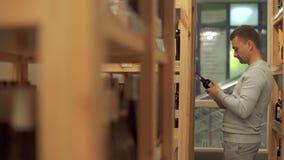 Uomo bello che guarda le iscrizioni sulla bottiglia di vino Il cliente sta scegliendo la bevanda nel negozio dell'alcool video d archivio