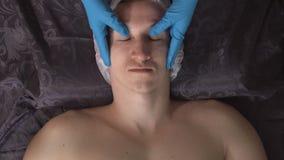 Uomo bello che ha massaggio di fronte nel salone della stazione termale stock footage