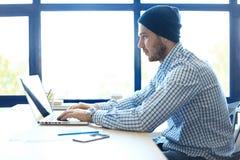 Uomo bello che lavora dal suo Ministero degli Interni Analizzi i business plan sul computer portatile Fondo vago, effetto del fil fotografie stock