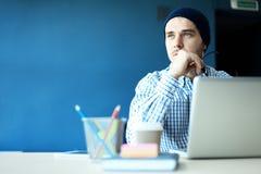 Uomo bello che lavora dal suo Ministero degli Interni Analizzi i business plan sul computer portatile Fondo vago, effetto del fil fotografia stock libera da diritti