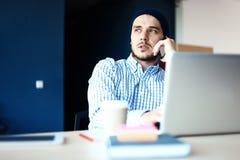 Uomo bello che lavora dal suo Ministero degli Interni Analizzi i business plan sul computer portatile Fondo vago, effetto del fil immagine stock libera da diritti
