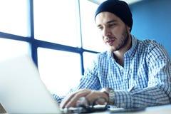 Uomo bello che lavora dal suo Ministero degli Interni Analizzi i business plan sul computer portatile Fondo vago, effetto del fil immagini stock