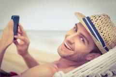 Uomo bello che manda un sms sull'amaca Fotografia Stock