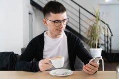 Uomo bello che mangia caffè e che per mezzo dello smartphone alla caffetteria immagini stock