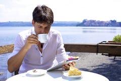 Uomo bello che mangia prima colazione sul lago Fotografia Stock