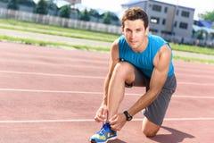 Uomo bello che merletta le sue scarpe da tennis Fotografie Stock