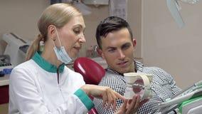 Uomo bello che mostra i pollici sulla seduta nella sedia dentaria, parlante con suo dentista archivi video