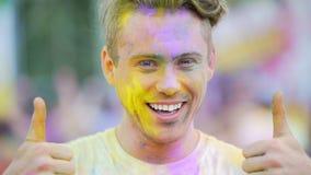 Uomo bello che mostra il pollice in su, fronte felice coperto in polvere colorata, primo piano video d archivio