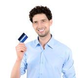 Uomo bello che mostra la carta di credito isolata Fotografia Stock