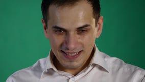 Uomo bello che mostra le emozioni differenti Fine in su Fondo verde archivi video