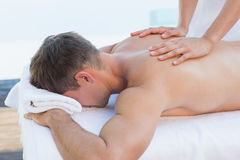 Uomo bello che ottiene un poolside di massaggio fotografie stock libere da diritti
