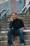 Uomo bello che parla emozionalmente sul telefono che si siede sui punti di pietra in europeo anziano in città Fotografie Stock