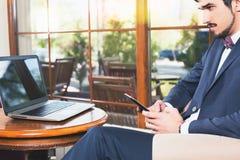 Uomo bello che per mezzo di un telefono cellulare e di un computer portatile al caffè Immagine Stock Libera da Diritti